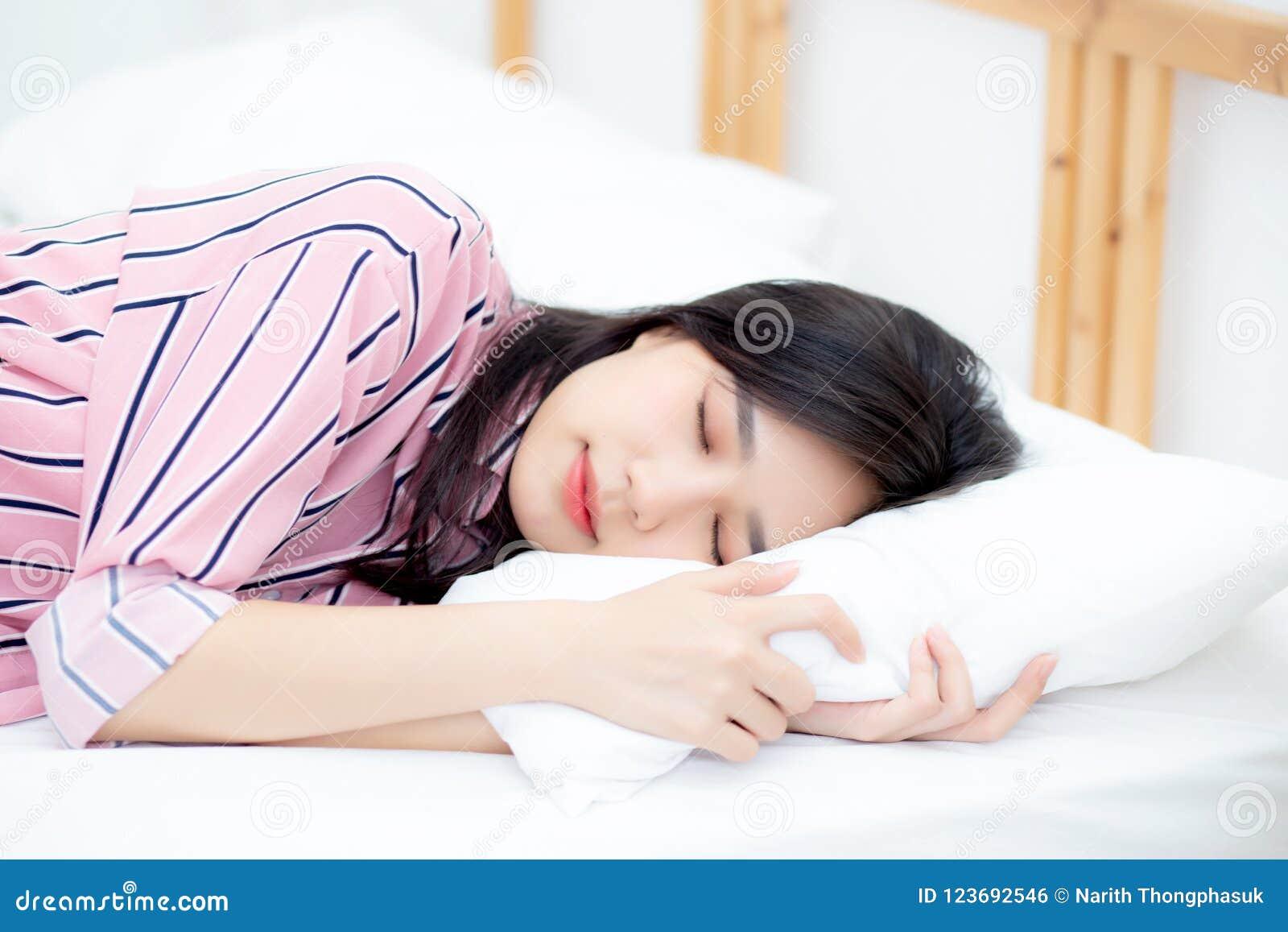 Portret van mooie Aziatische jonge vrouwenslaap die in bed met hoofd op hoofdkussen comfortabel en gelukkig met vrije tijd liggen