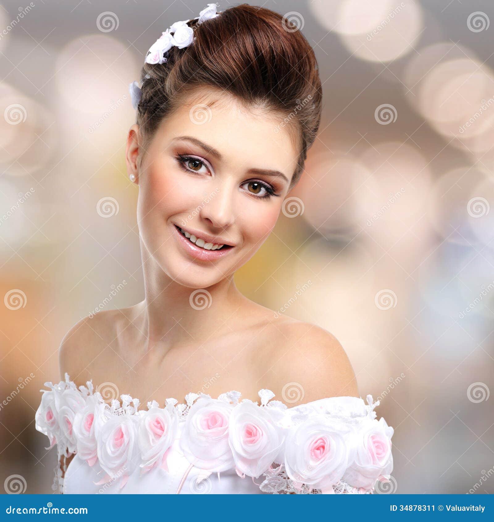 Portret van mooie glimlachende bruid in huwelijkskleding