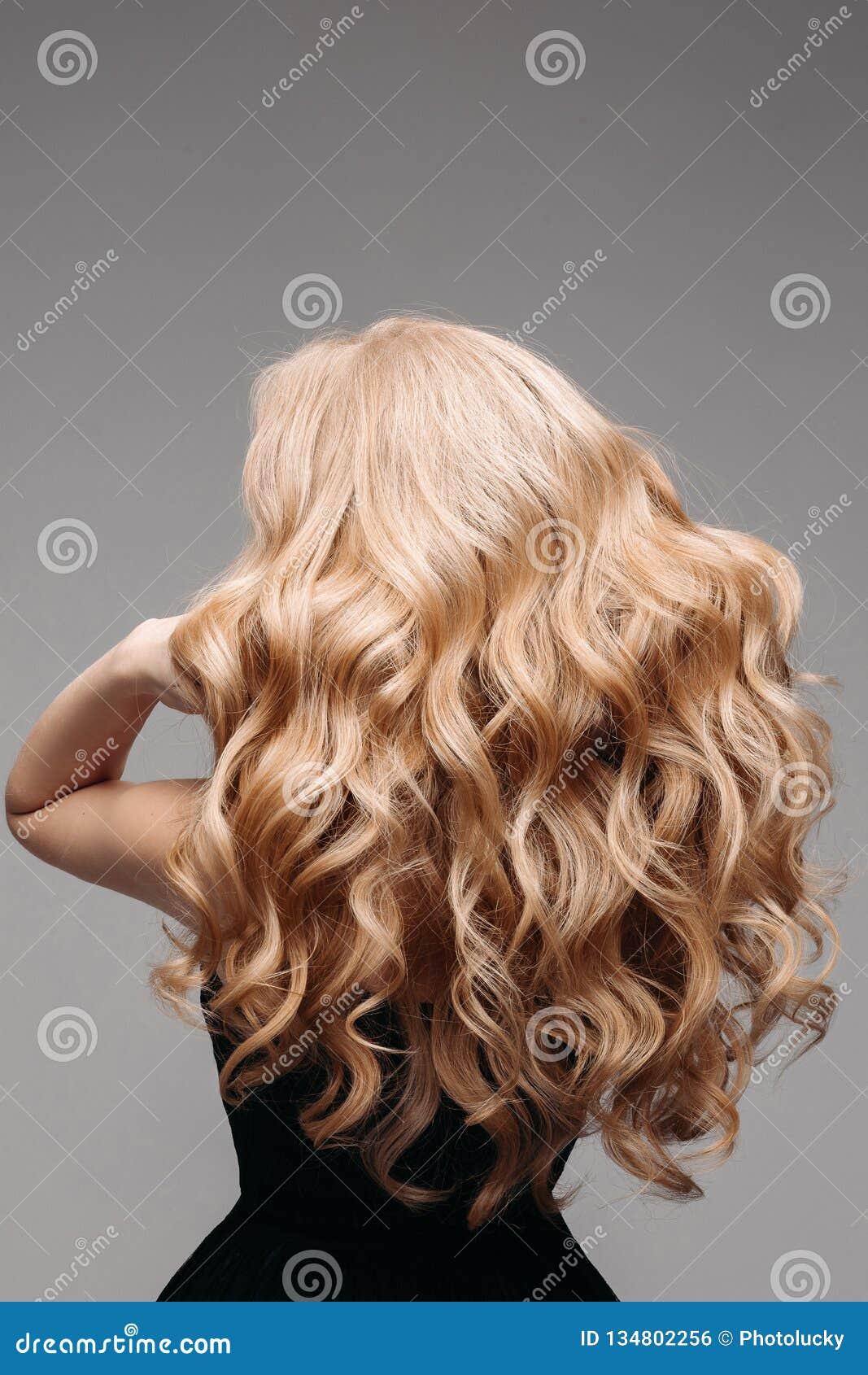 Portret van Mooie Jonge Blonde Vrouw met Lang Golvend Haar Achter mening