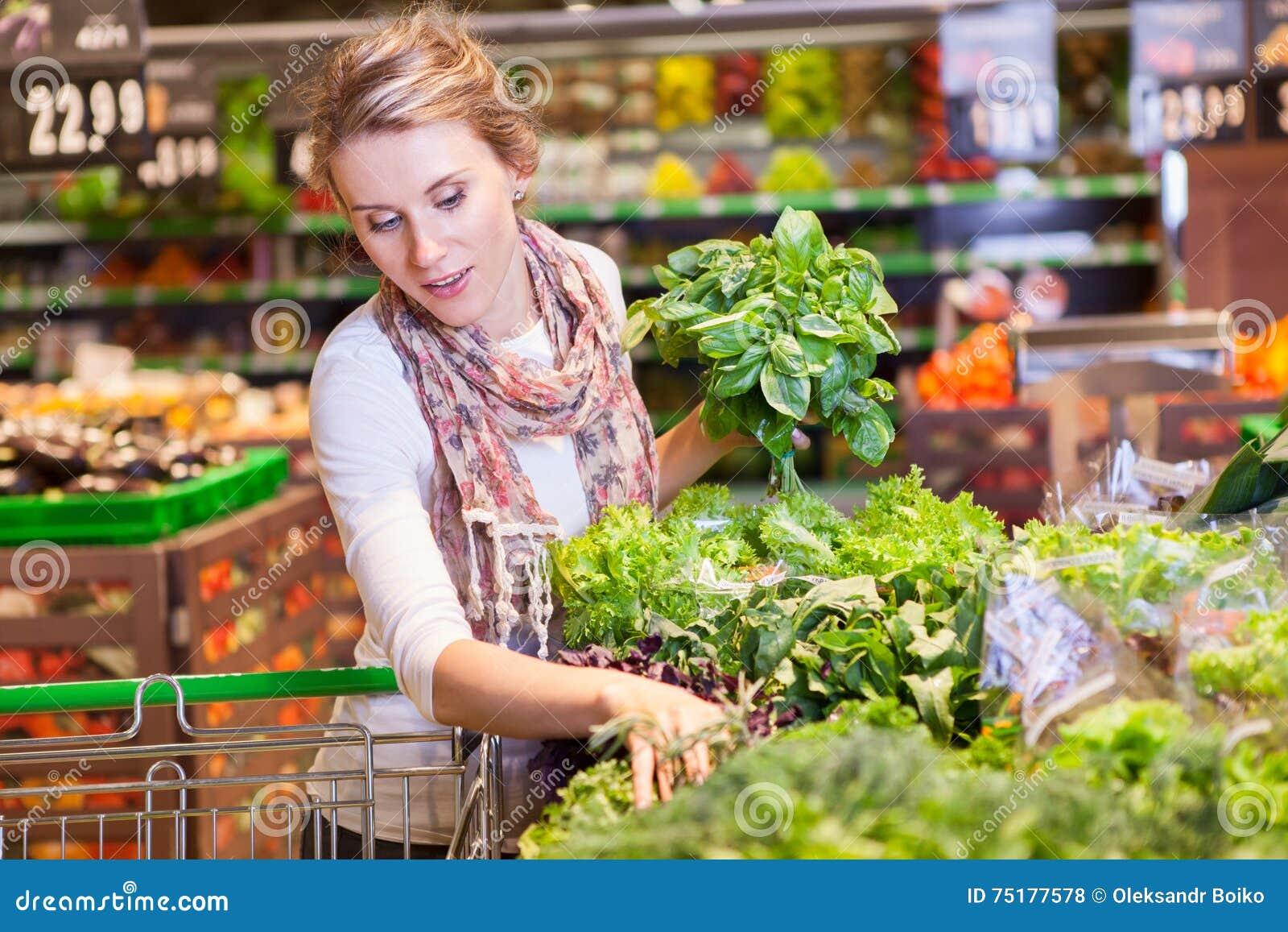 Portret van mooie jonge vrouw die groene bladgroente kiezen