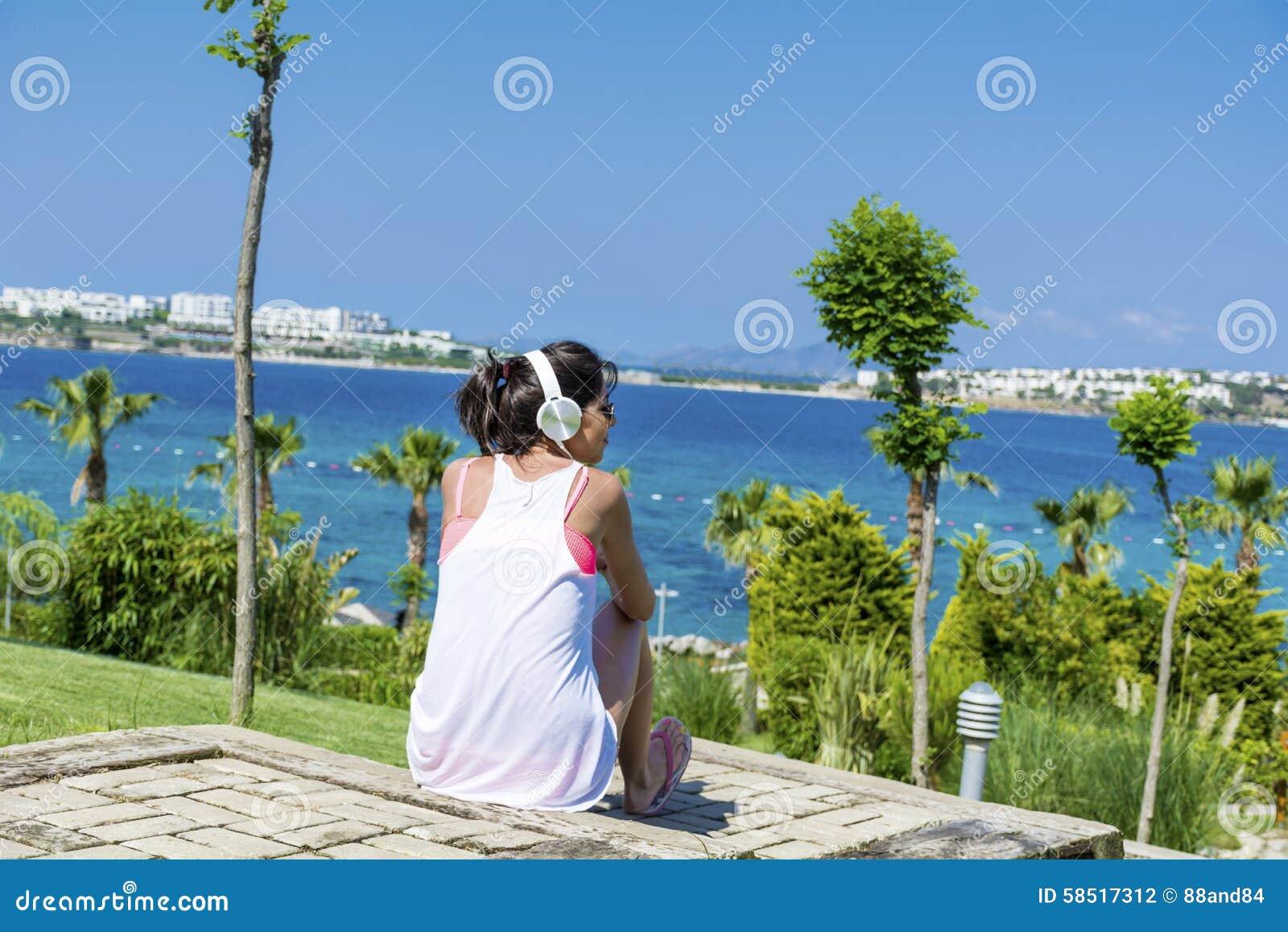 Portret van mooie jonge vrouw het luisteren muziek op een overzeese achtergrond
