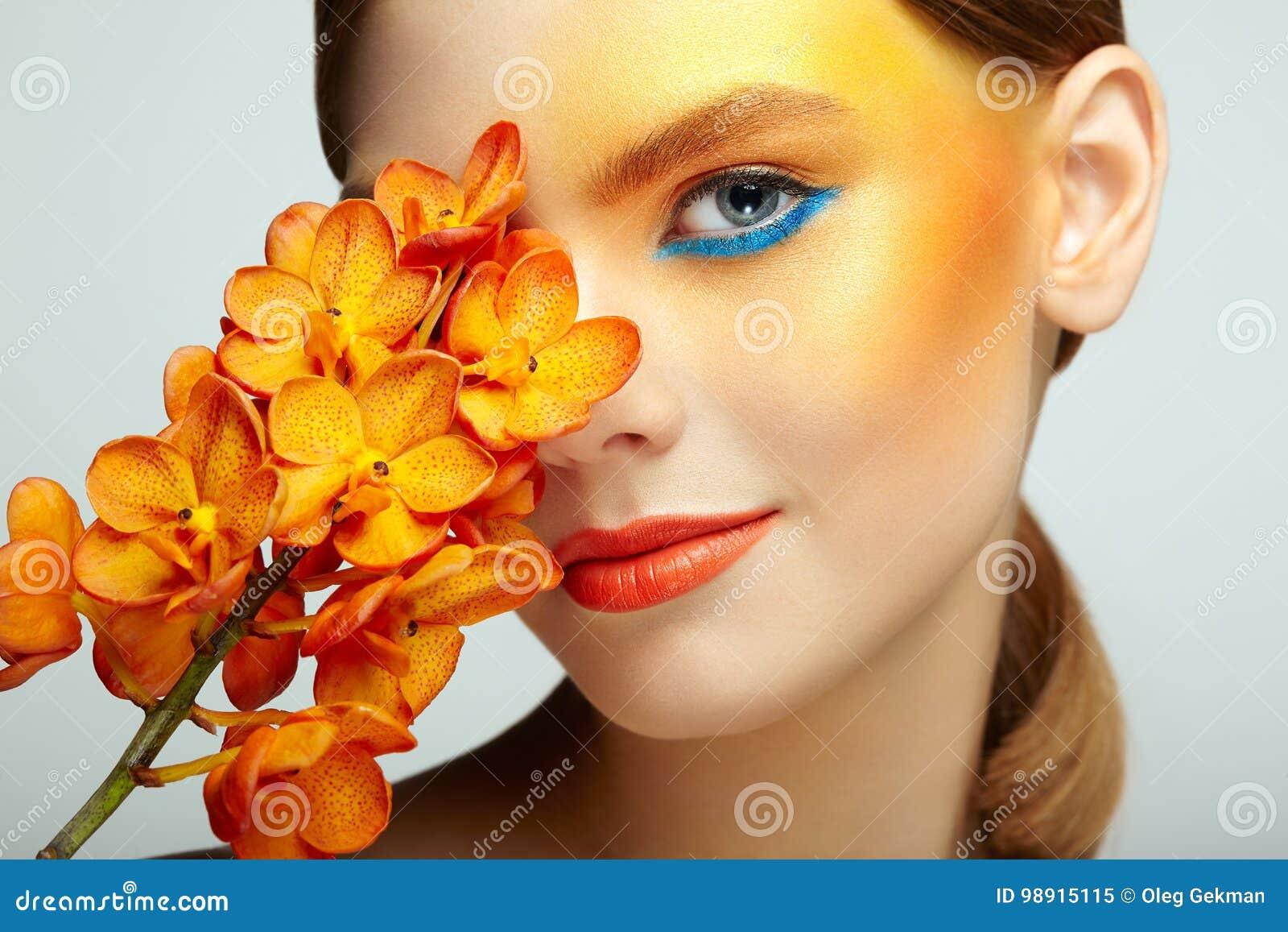 Portret van mooie jonge vrouw met orchidee
