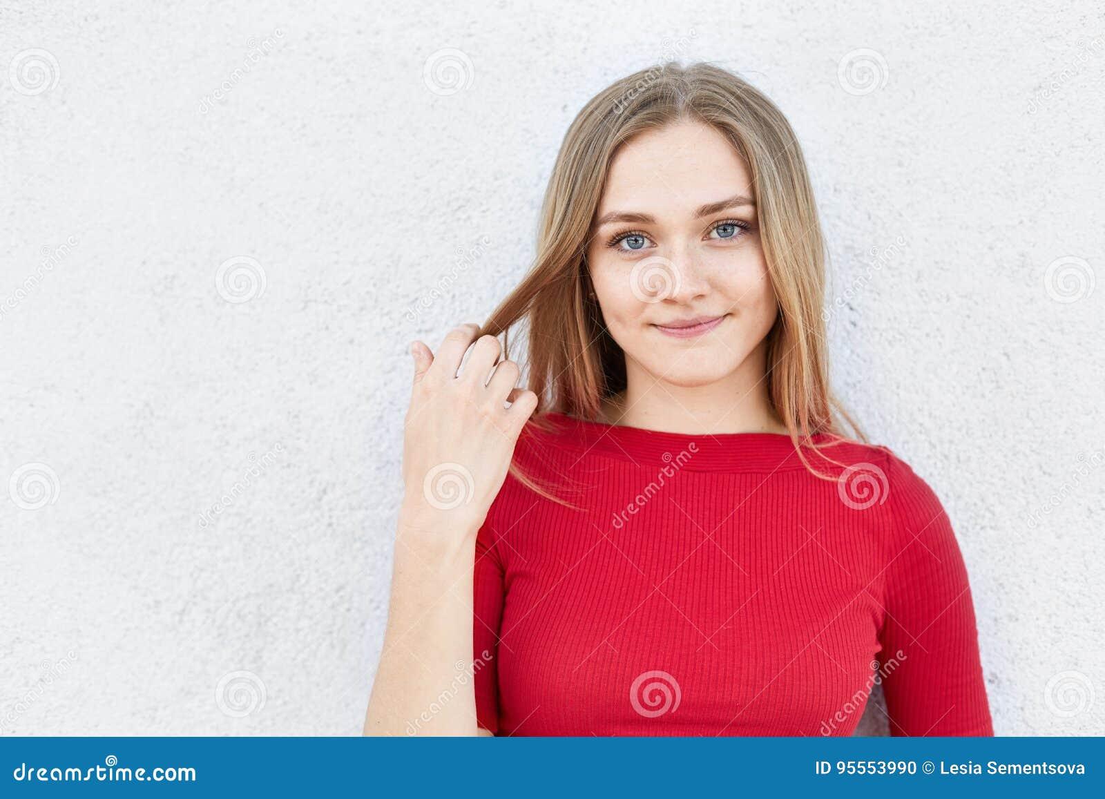 Portret van mooie jonge vrouw met recht blondehaar, verleidelijke ogen en dikke lippen die tevreden uitdrukking hebben terwijl he