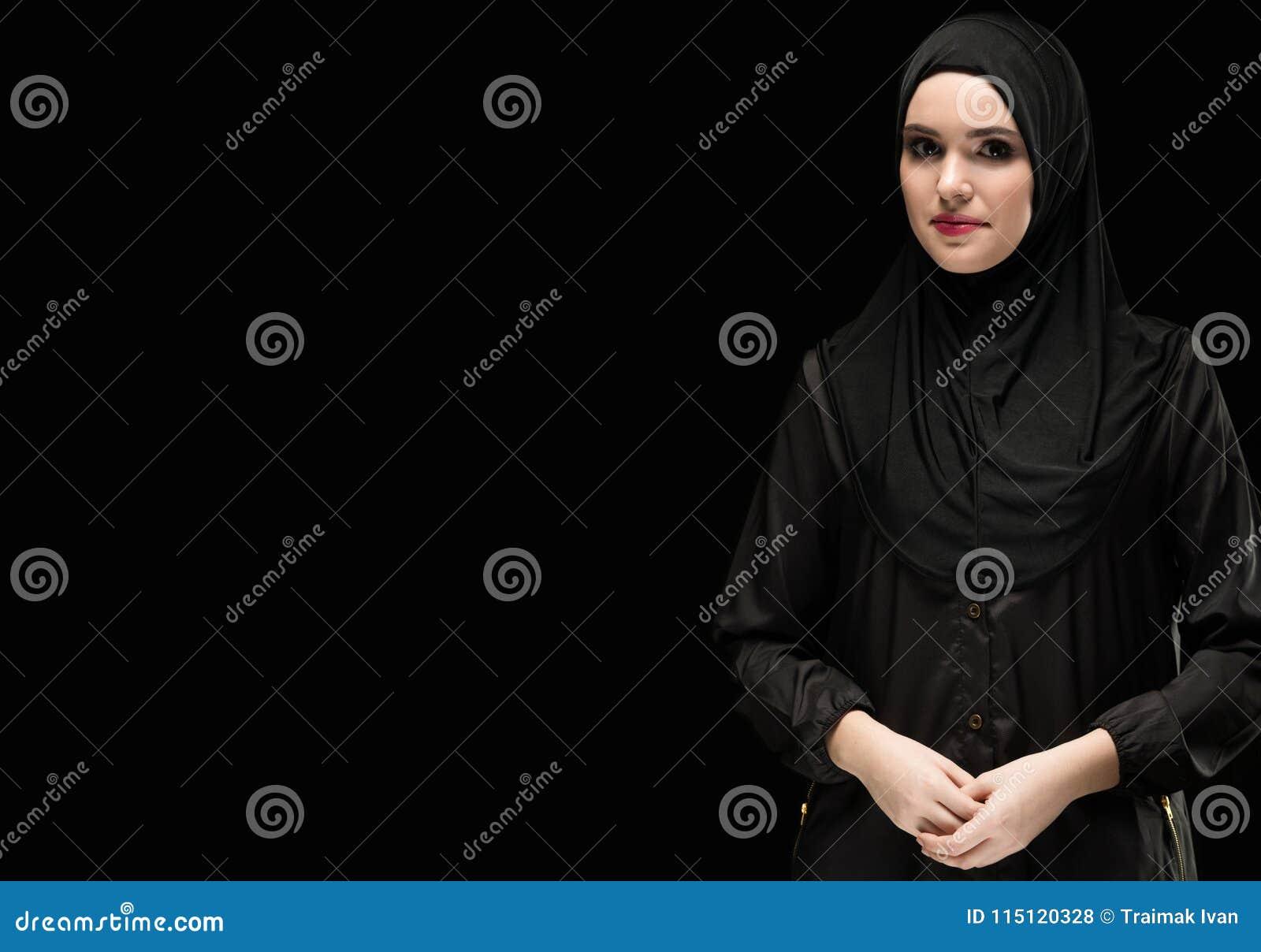 Portret van mooie positieve jonge moslimvrouw die zwarte hijab dragen als conservatief manierconcept met hand op hand