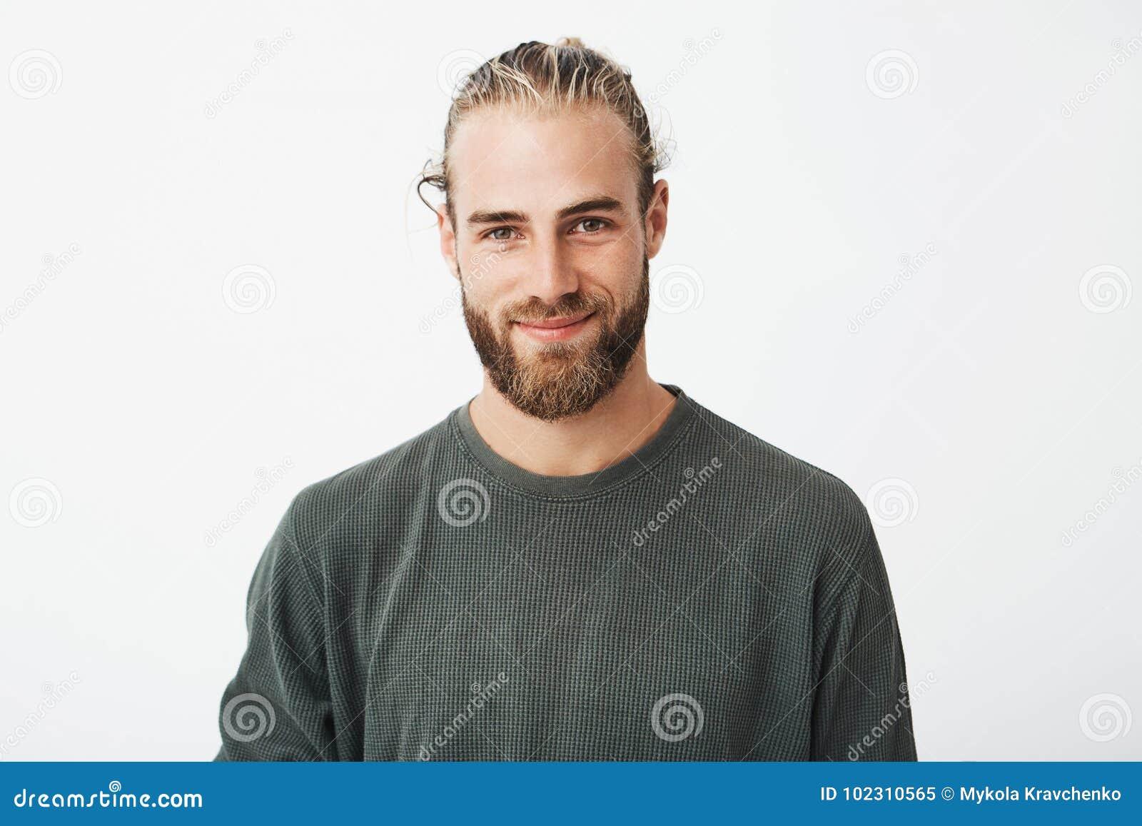 Portret van mooie rijpe blonde gebaarde kerel met in kapsel in toevallig grijs en overhemd die in camera glimlachen kijken