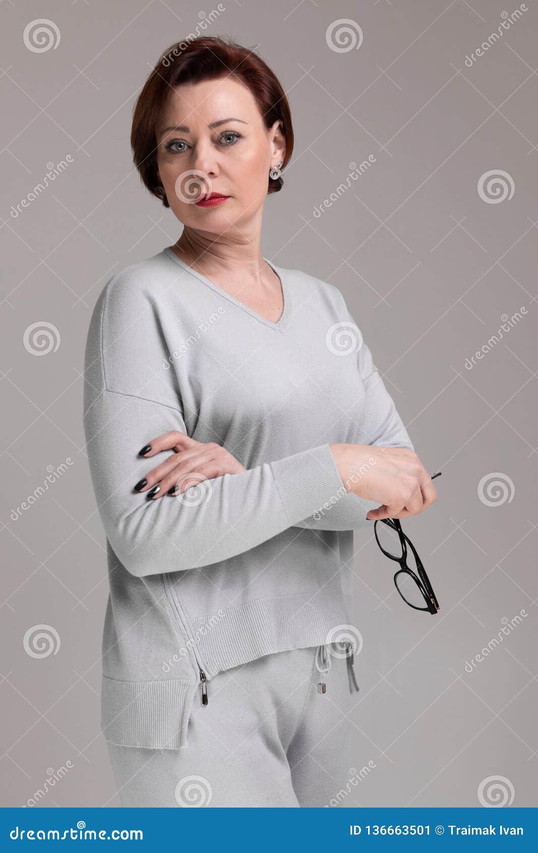 Portret van mooie vrouw in lichte die kleren met glazen ter beschikking op lichte achtergrond wordt geïsoleerd