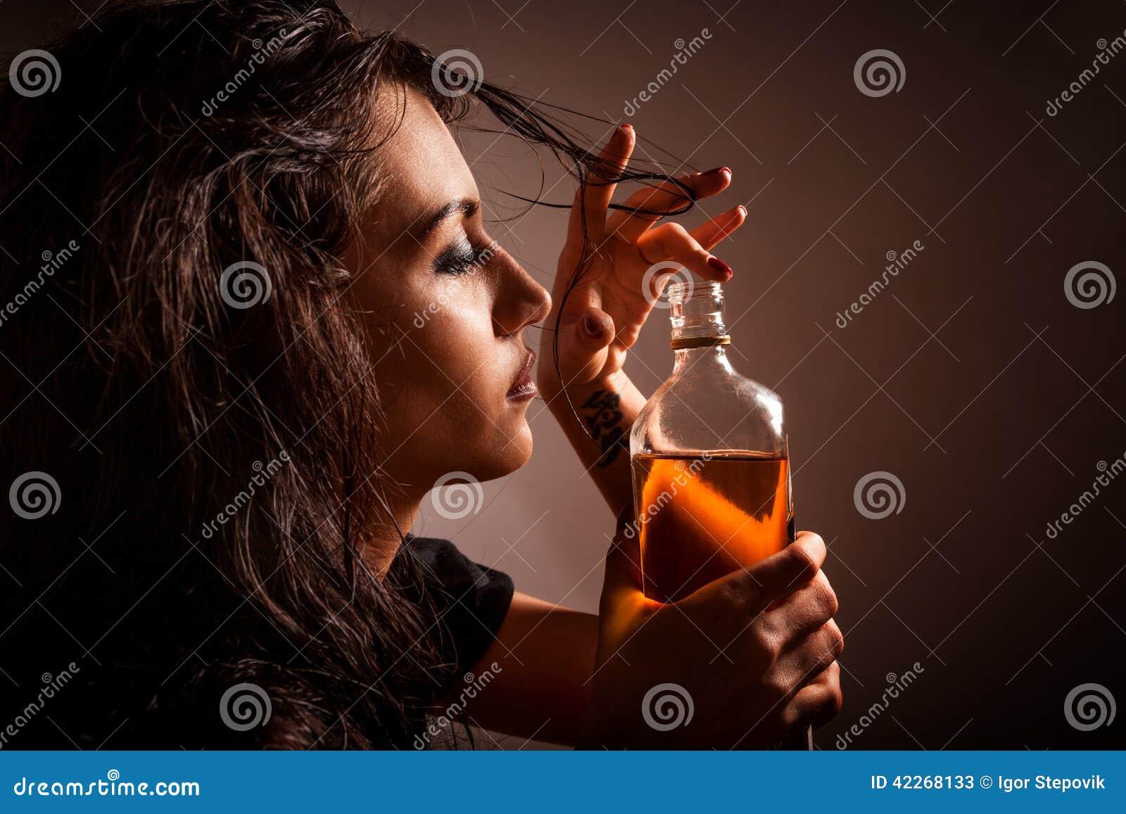 Portret van mooie vrouw met fles van alcoholdrank