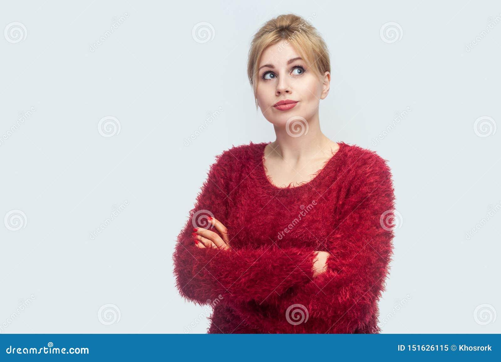 Portret van nadenkende mooie jonge blonde vrouw in rode blouse die zich met gekruiste wapens bevinden, weg en wat denken om te do
