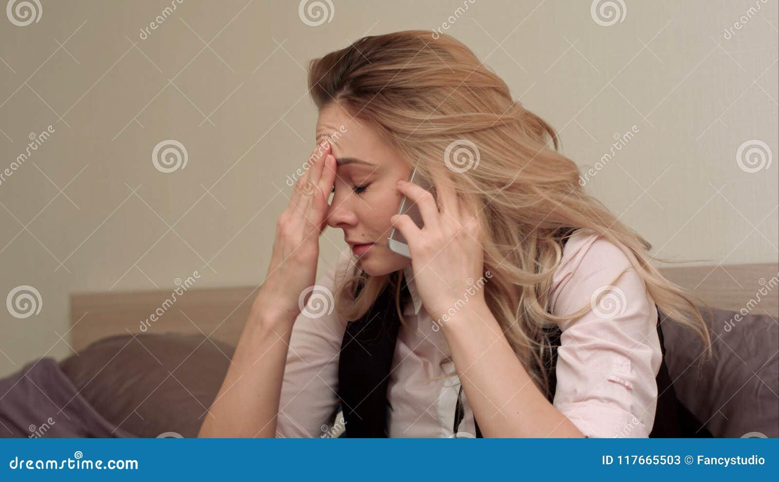 Portret van ongelukkige jonge vrouw die geërgerd telefoongesprek thuis maken