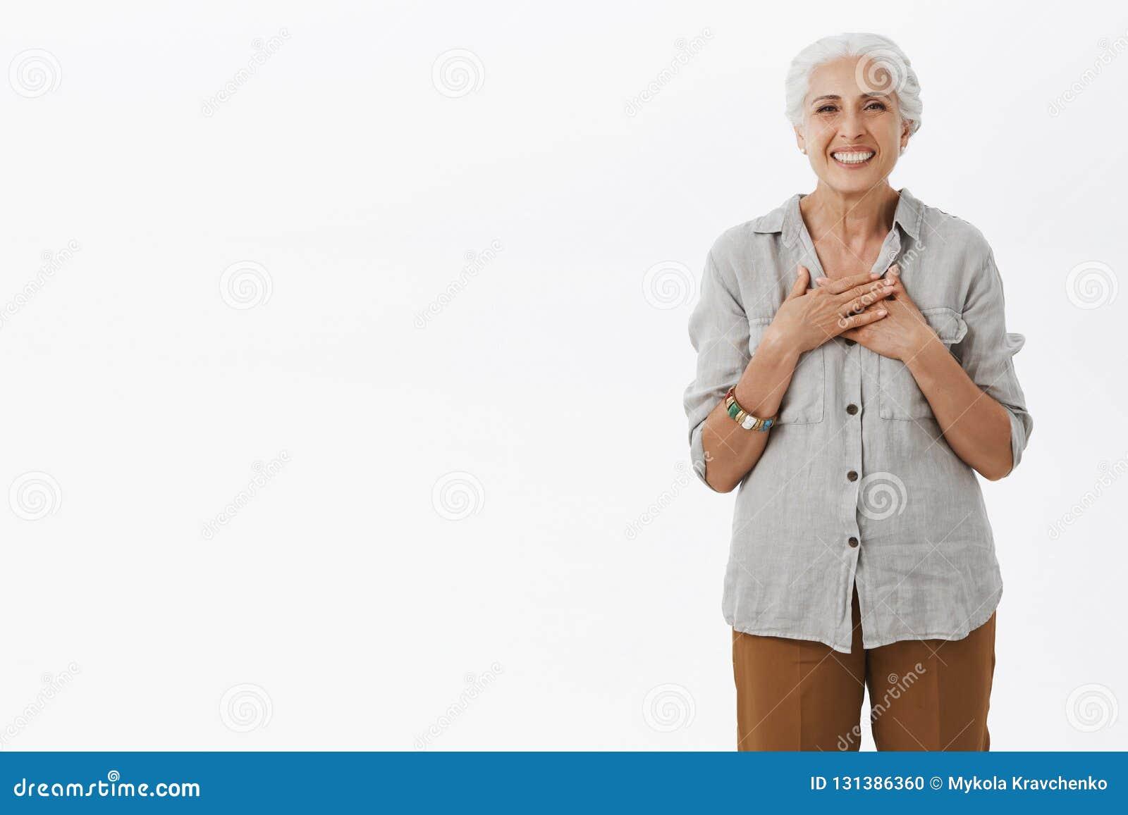 Portret van opgetogen charmant oud wijfje met de grijze gekamde palmen van de haarholding op borst met tevreden en dankbare gliml