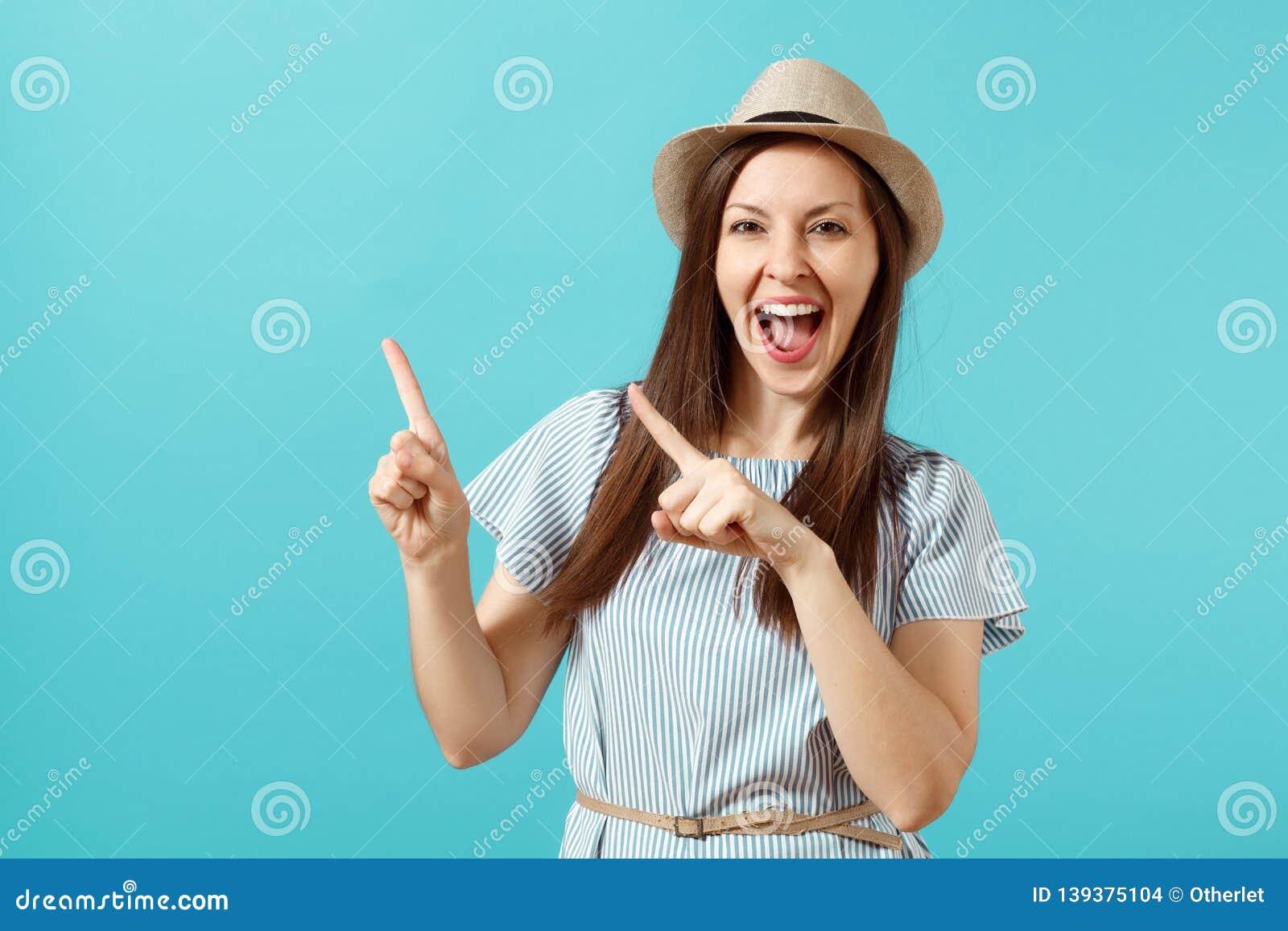Portret van opgewekte jonge elegante vrouw die kleding, de hoed dragen die van de strozomer wijsvingers op geïsoleerde exemplaarr
