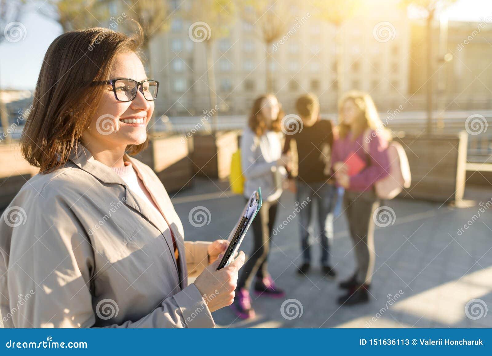 Portret van rijpe glimlachende vrouwelijke leraar in glazen met klembord, outdor met een groep tienersstudenten