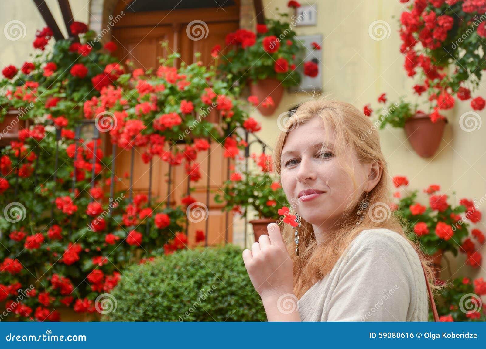 Portret van roodharige vrouw voor rode bloemen