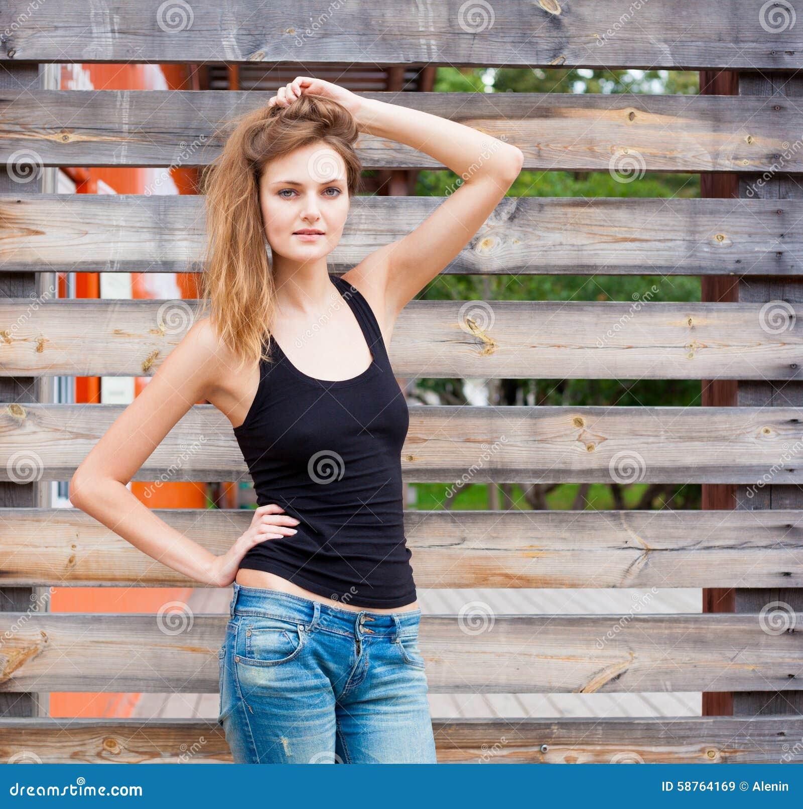 Portret van In Sexy Meisje Status bij de Oude Houten Muurachtergrond Stedelijk Manierconcept De ruimte van het exemplaar