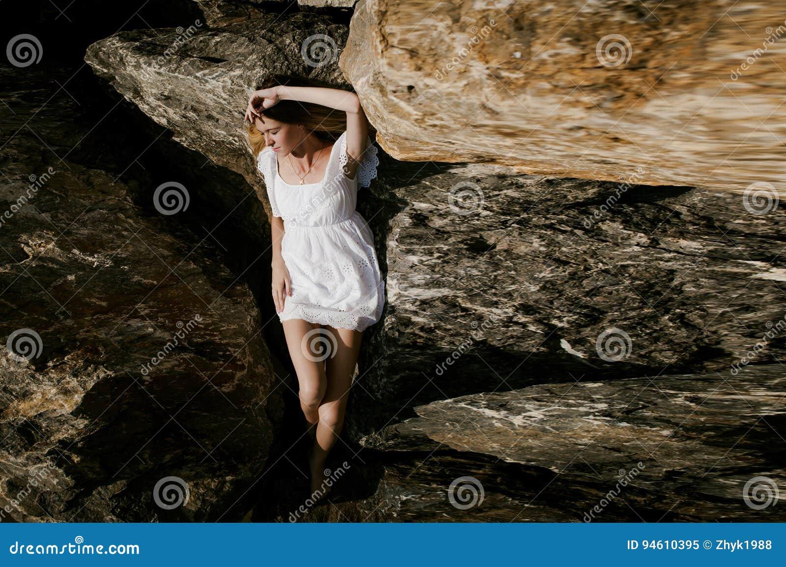 Portret van slanke jonge vrouw op stenen dichtbij het overzees