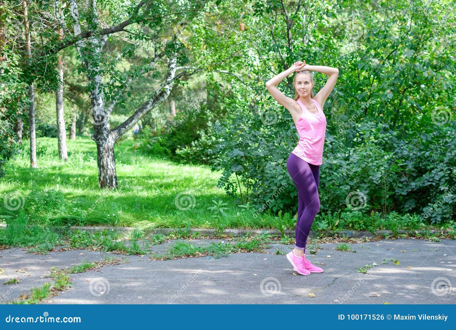 Portret van sportieve vrouw die uitrekkende oefeningen in park doen alvorens op te leiden Vrouwelijke atleet die voor jogging voo