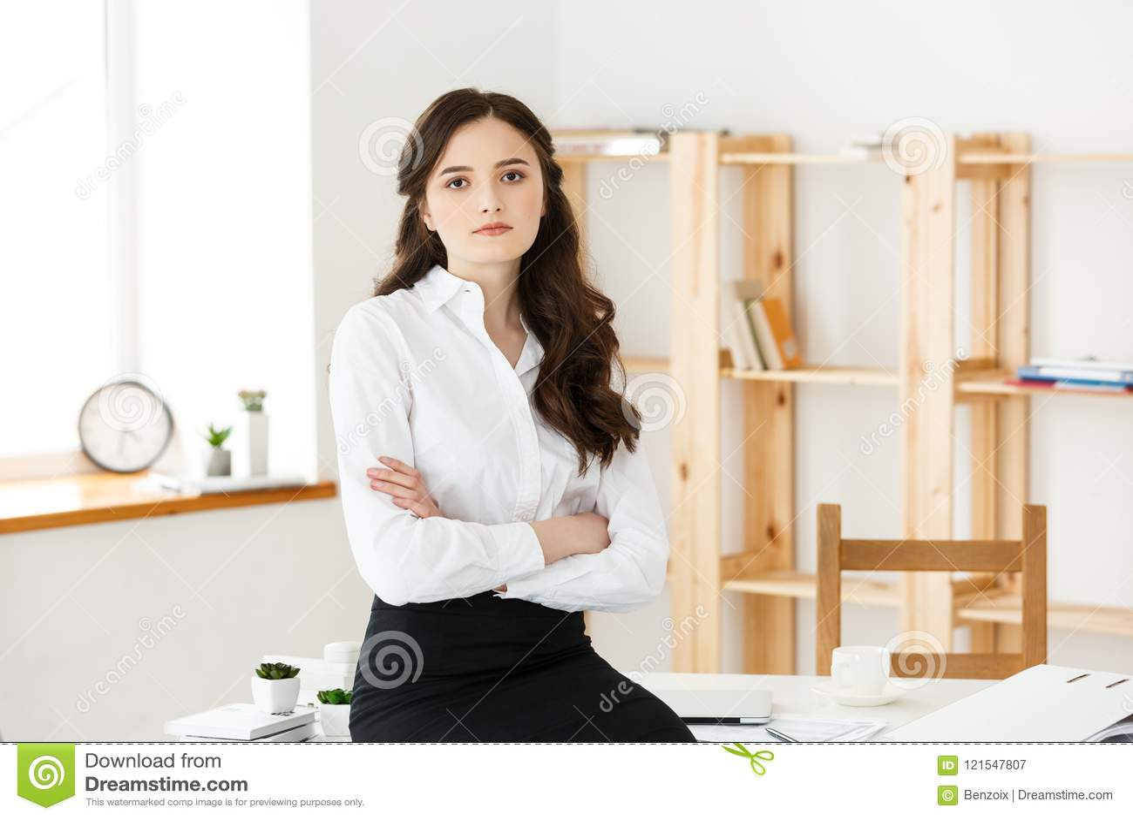 Portret van succesvolle die onderneemster met wapens op het kantoor worden gekruist Rijpe professionele vrouw die camera bekijken