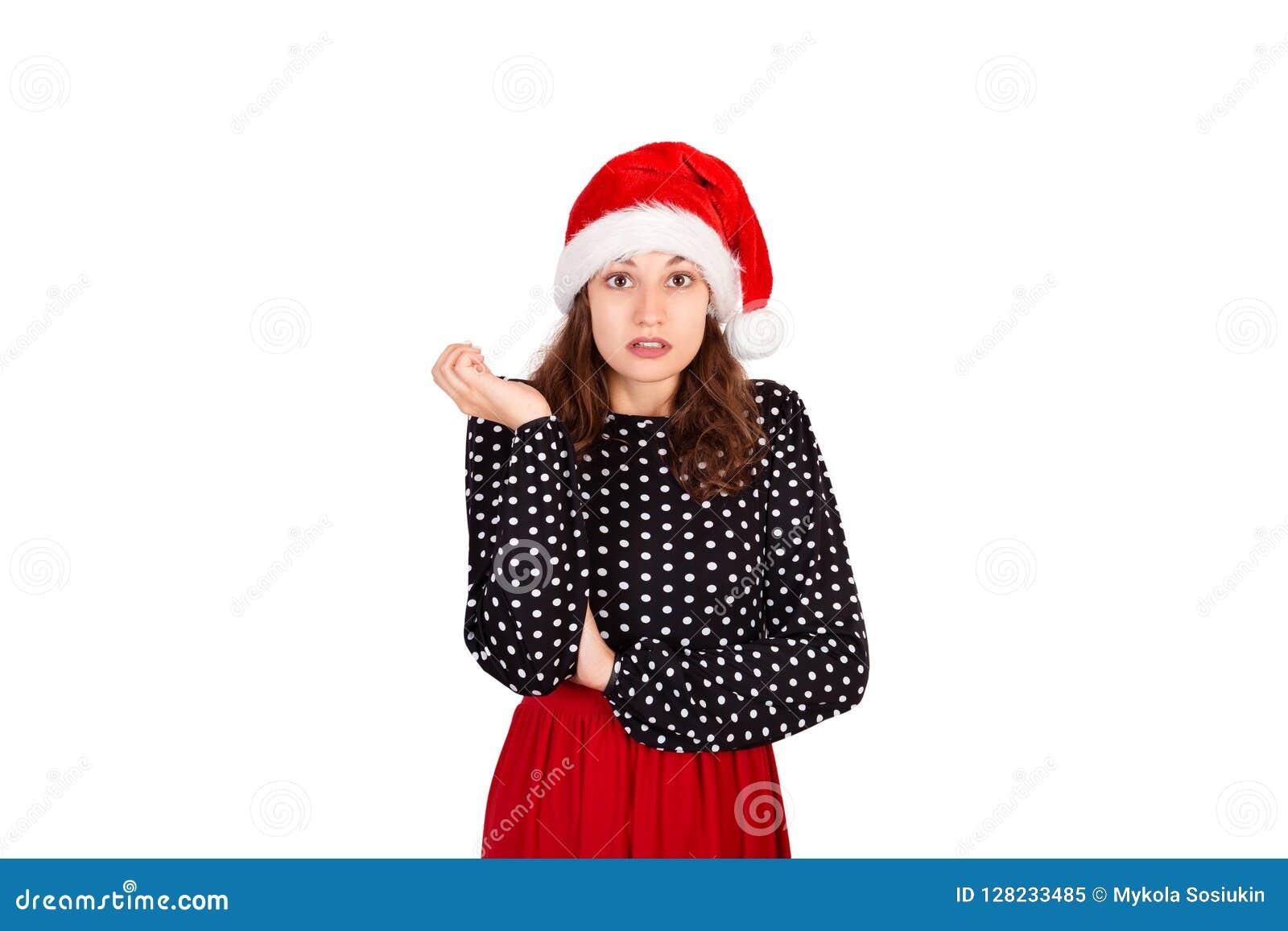 Portret van teleurgesteld boos leuk wijfje in kleding emotioneel meisje in Kerstmishoed van de Kerstman dat op witte achtergrond