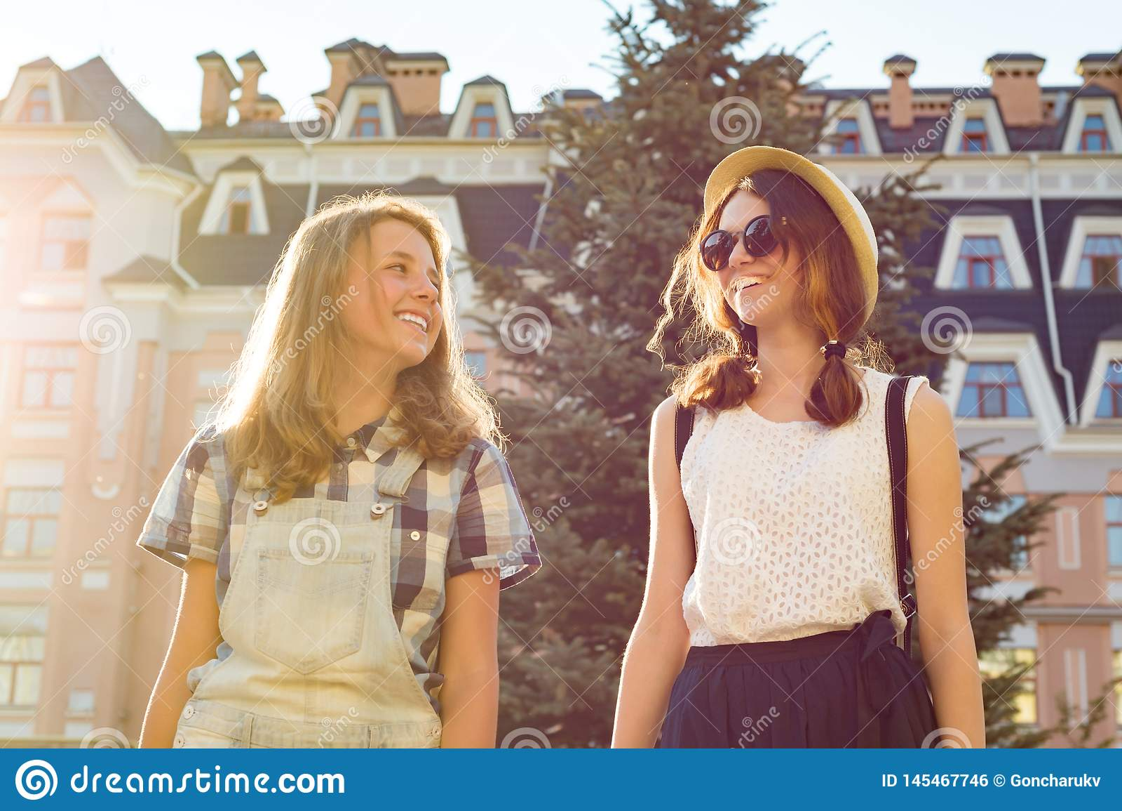 Portret van twee glimlachende mooie meisjes, tieners 13, 14 jaar oud, close-up, meisjes het spreken lachend en lopend in de zomer
