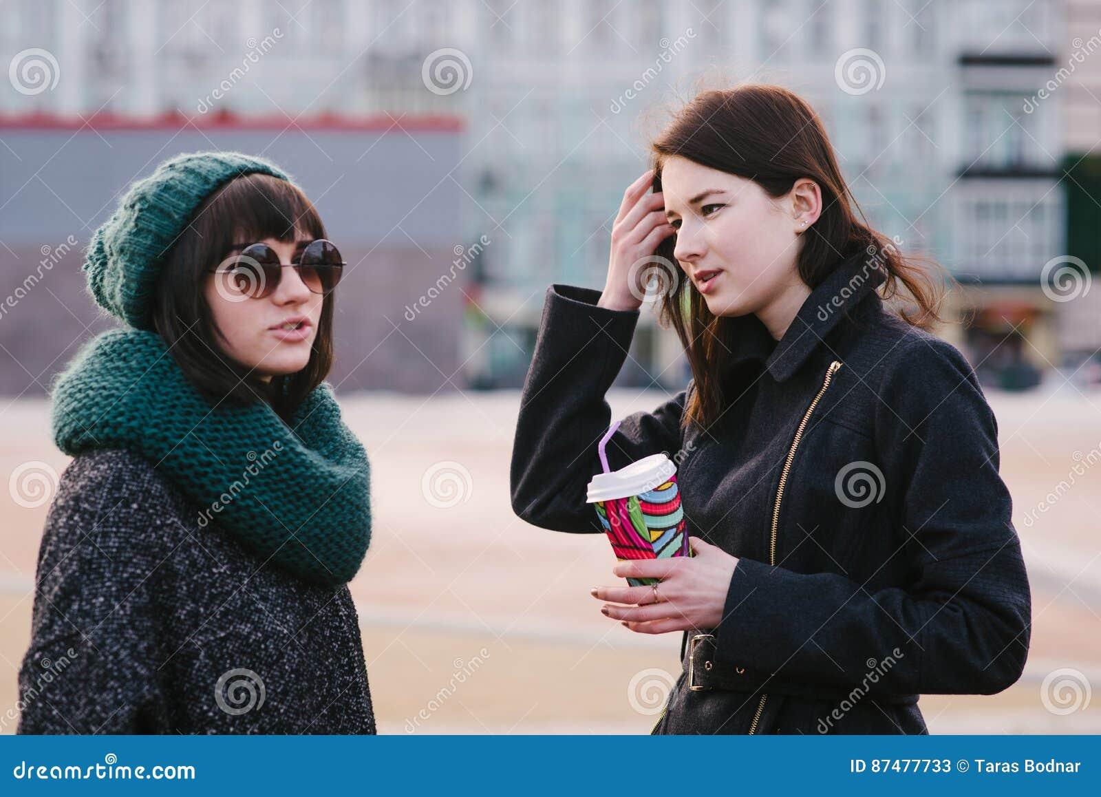 Portret van twee modieuze en mooie meisjes die zich op het midden van de stadsstraat bevinden