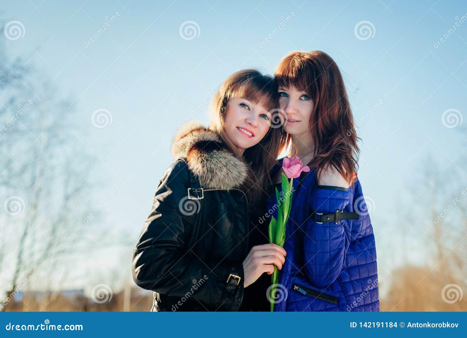 Portret van twee mooie meisjes tegen een duidelijke de lentehemel