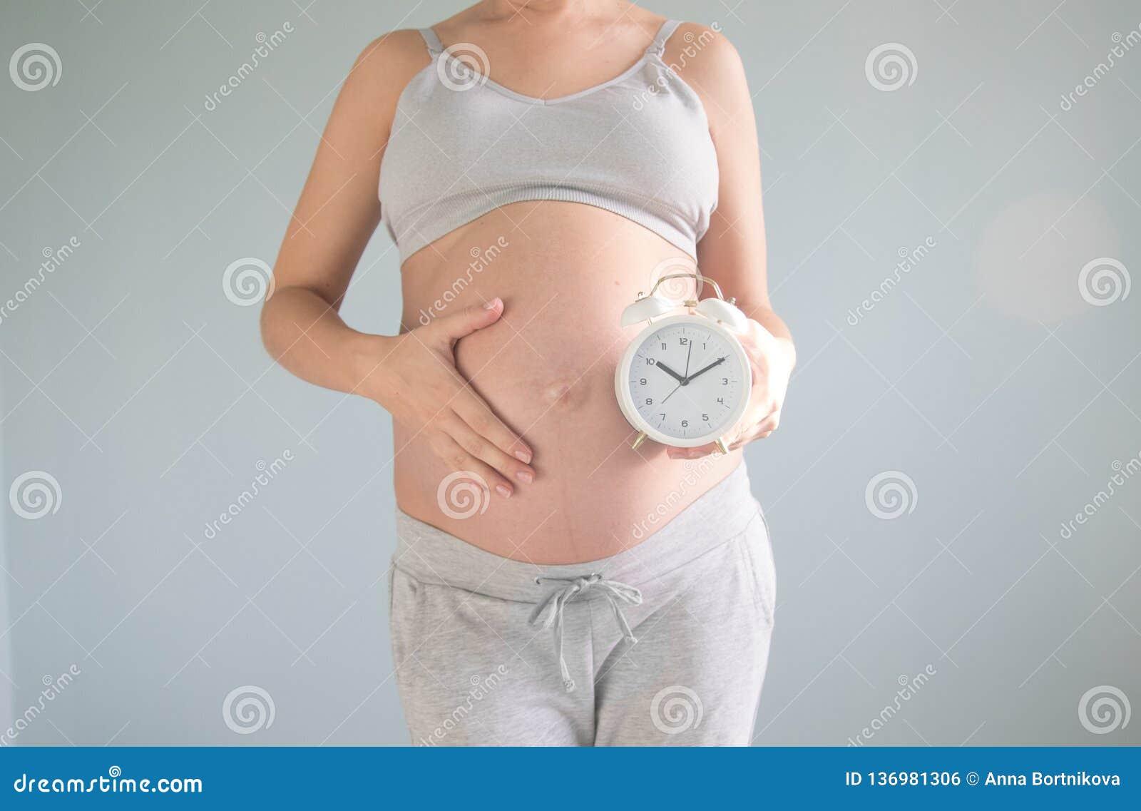 Portret van verbaasde zwangere de muurklok van de vrouwenholding