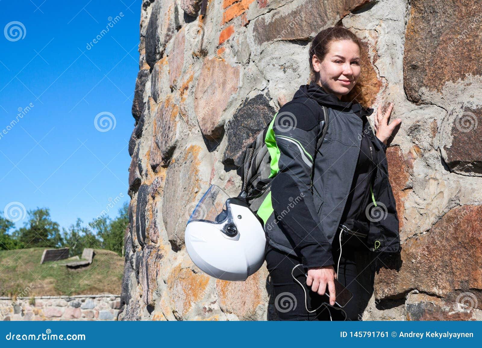 Portret van vermoeide motorrijdervrouw die dichtbij steenmuur na landloper een vesting in kleding rusten, met rugzak en helm in b