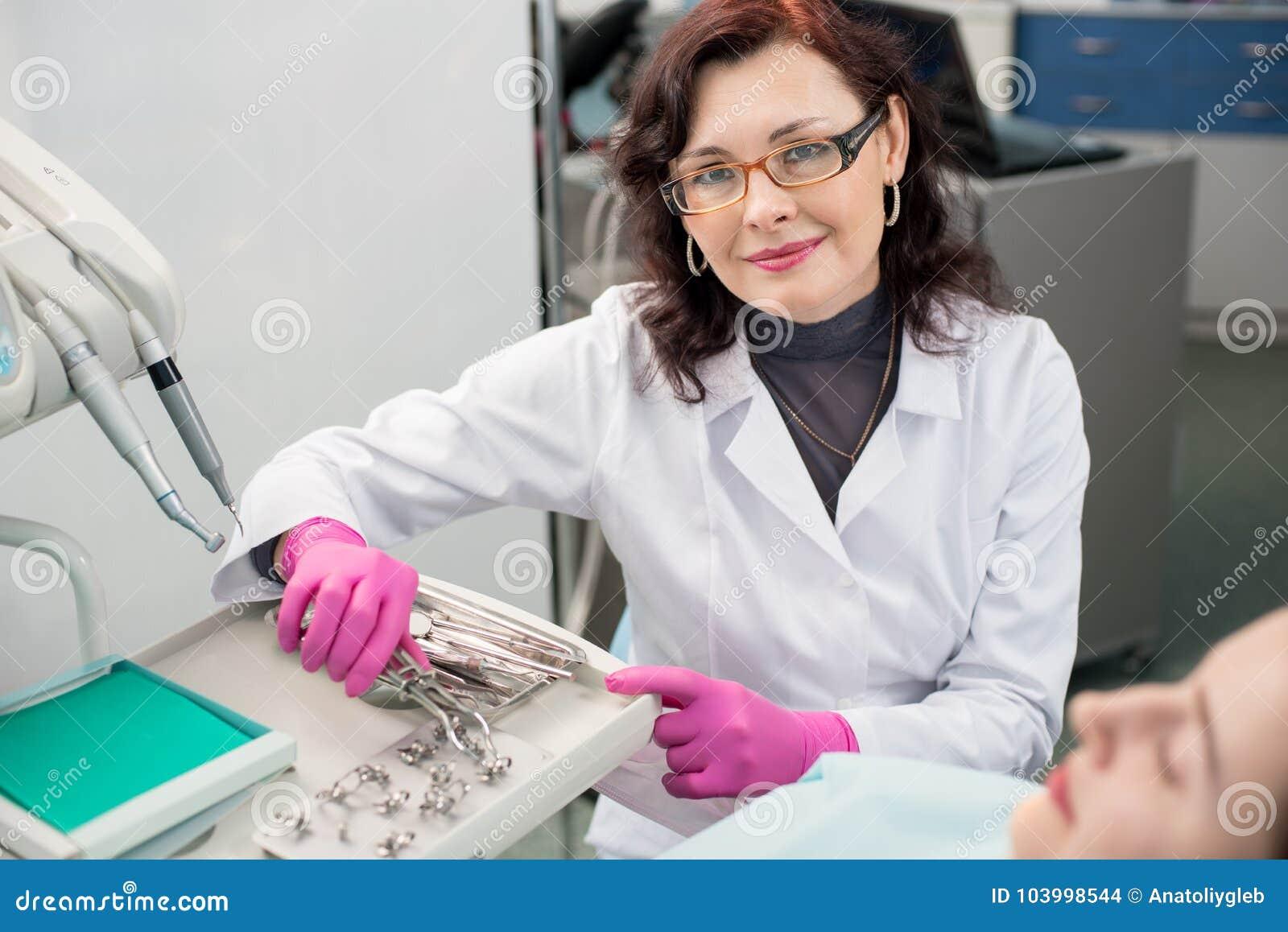 Portret van vriendschappelijke vrouwelijke tandarts met vrouwelijke patiënt in het tandbureau tandheelkunde Tand apparatuur
