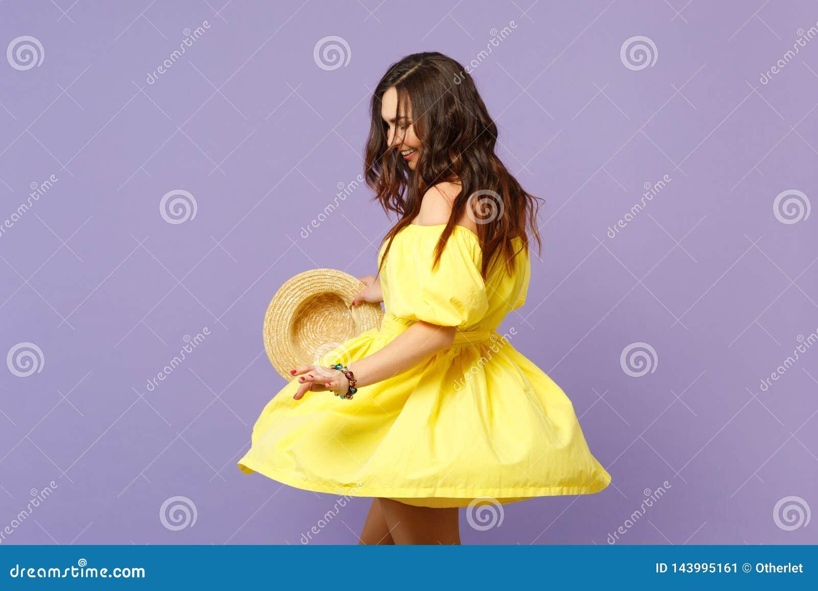 Portret van vrij glimlachende jonge vrouw die in gele de zomerhoed van de kledingsholding, wervelen geïsoleerd op pastelkleur nee