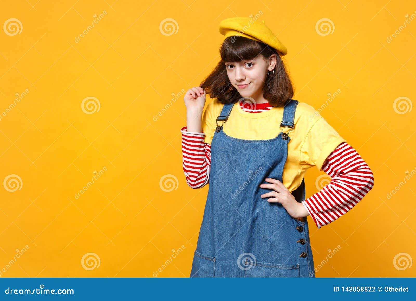 Portret van vrij heldere meisjestiener in Frans die baret en denim sundress holdingshaar op gele muur wordt geïsoleerd