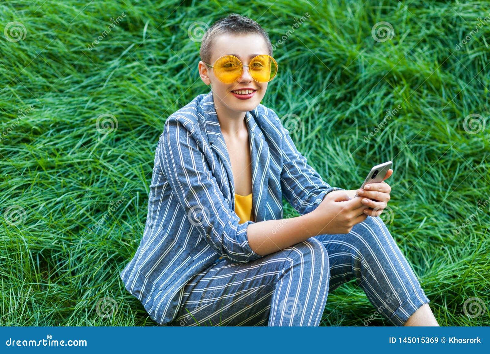 Portret van vrij jonge korte haarvrouw die in toevallig blauw gestreept kostuum, gele glazen op gras zitten die haar smartphone h