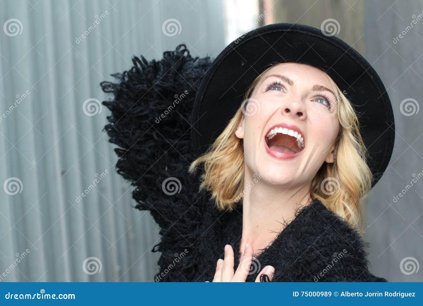 Portret van vrij vrolijke vrouw die zwarte bontkleding en moderne hoed in koude weerdag dragen Het lopen in openlucht in de winte