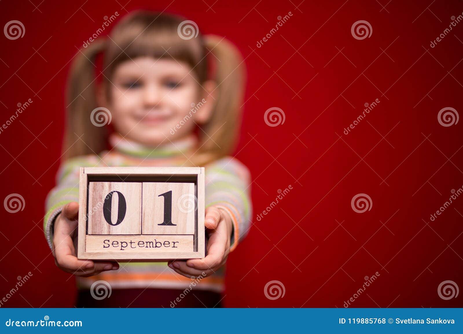 Portret van vrolijk die meisje op rode greep houten die kalender wordt geïsoleerd op fir september, nadruk op kalender wordt gepl