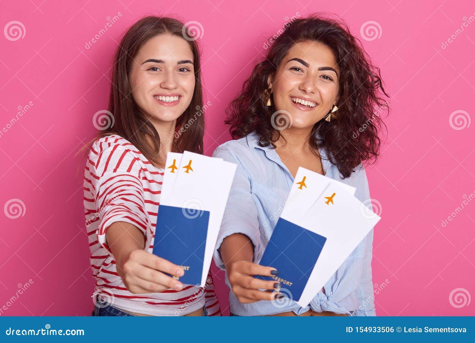 Portret van vrolijke leuke meisjes die in de zomer reizen, gekleed in vrijetijdskleding, die paspoorten met kaartjes tonen aan ca