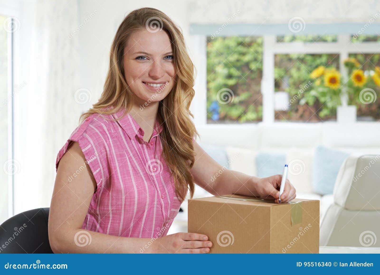 Portret van Vrouw die thuis Adres op Pakket schrijven