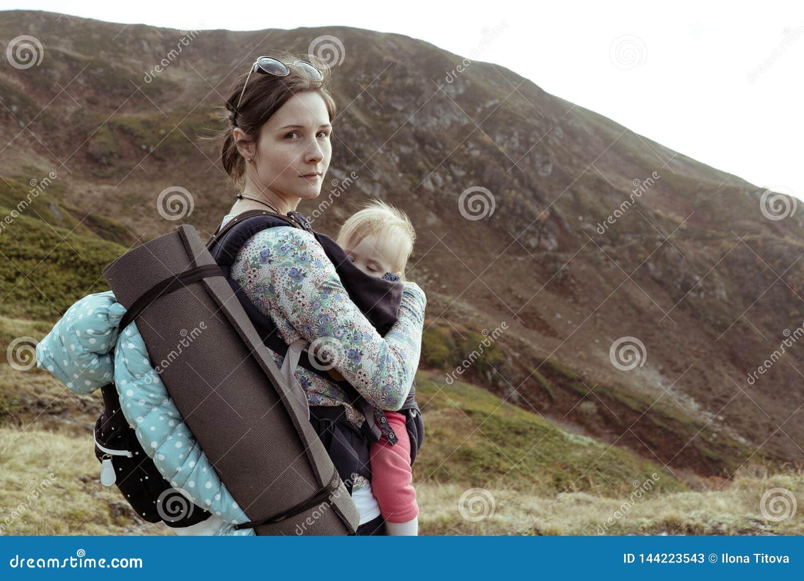 Portret van vrouw met baby en rugzak in berg