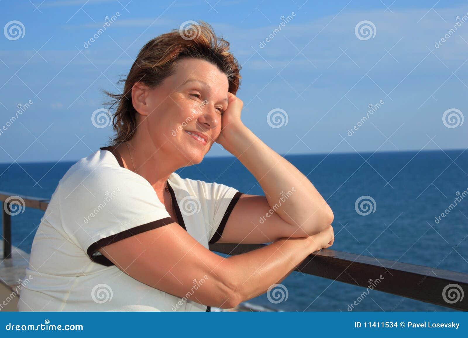 Portret van vrouw op middelbare leeftijd op balkon over overzees