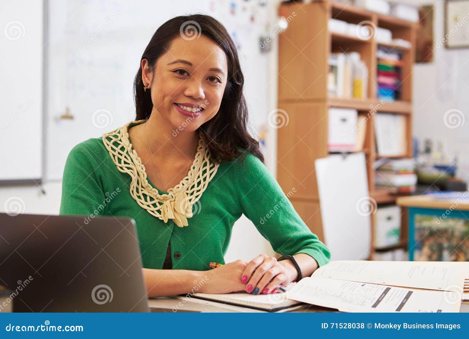 Portret van vrouwelijke Aziatische leraar bij haar bureau