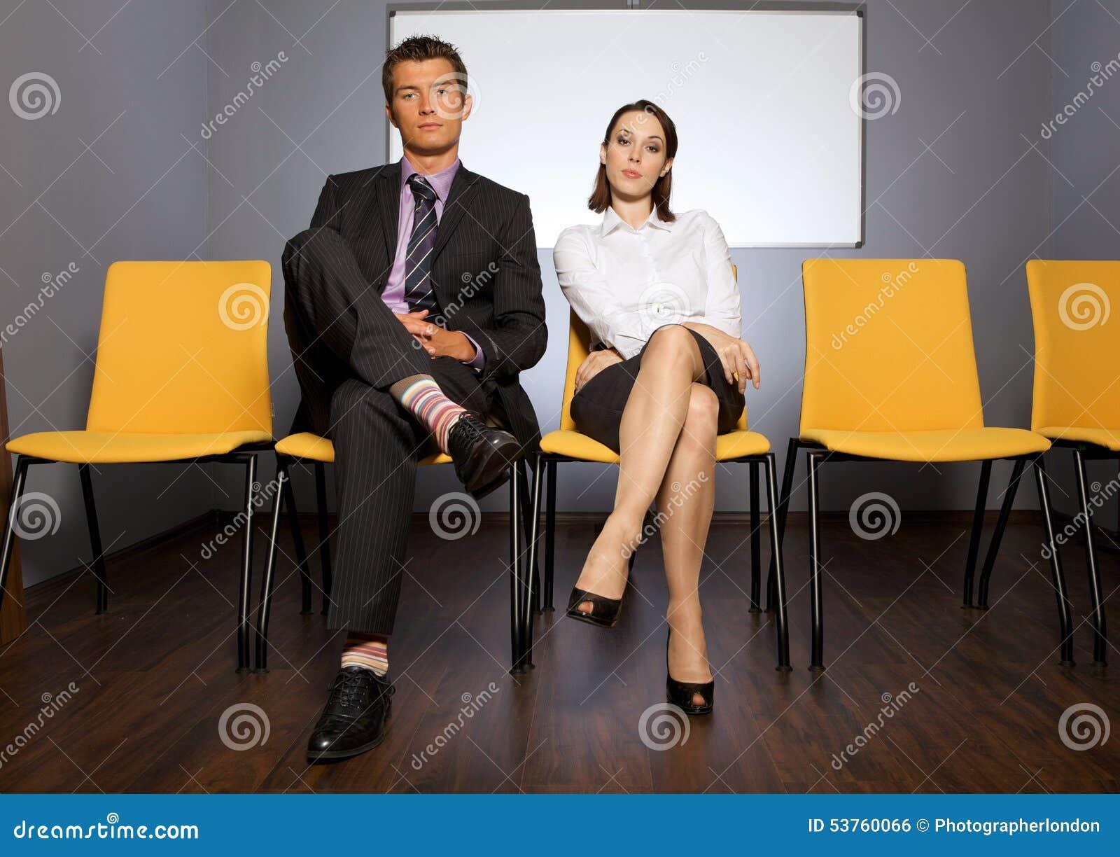 Portret van zakenman en onderneemsterzitting in wachtkamer