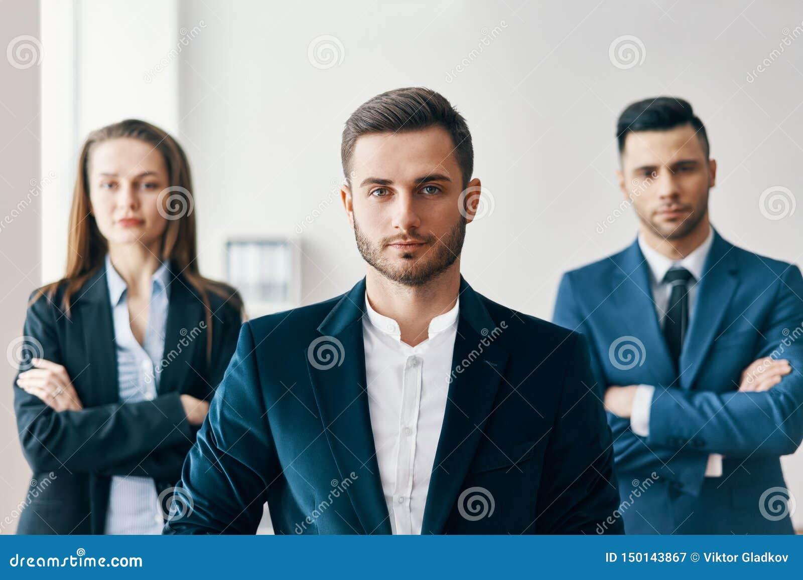 Portret van zekere knappe zakenman in bureau met zijn team op achtergrond