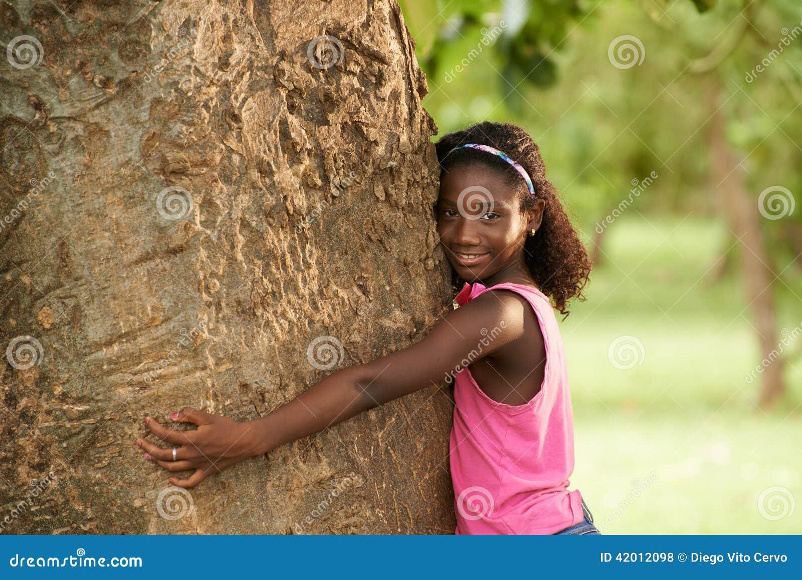 Portret van zwart ecologistmeisje die boom en het glimlachen koesteren