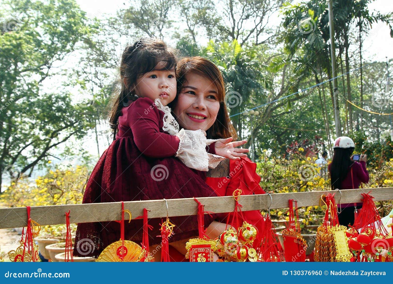 Portret Wietnamska kobieta i jej córka w czerwieni ubieramy z tradycyjnymi Wietnamskimi nowy rok dekoracjami na ulicie miasto
