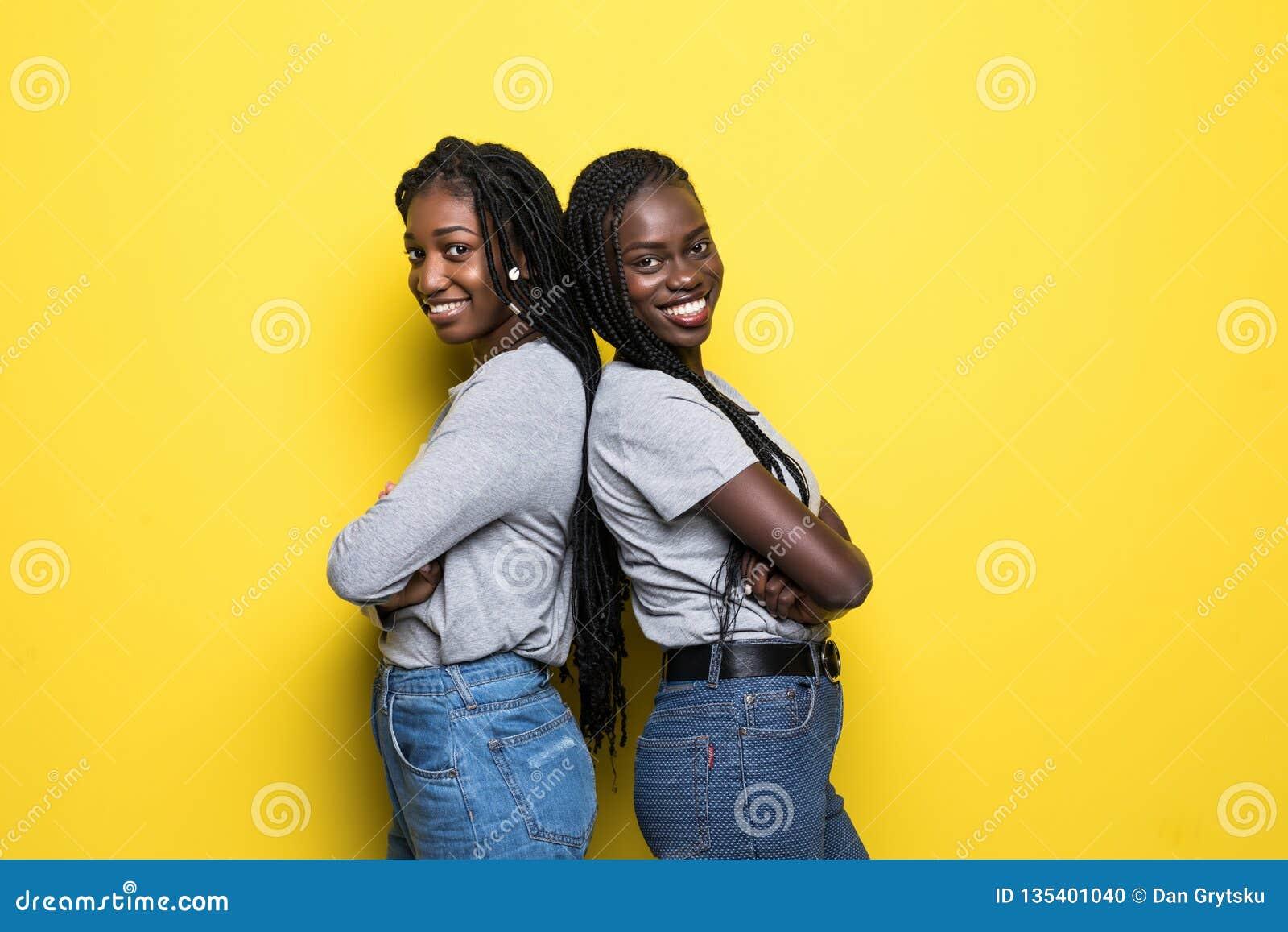 Portret wpólnie odizolowywający nad żółtym tłem dwa uśmiechniętej młodej afrykańskiej kobiety stoi