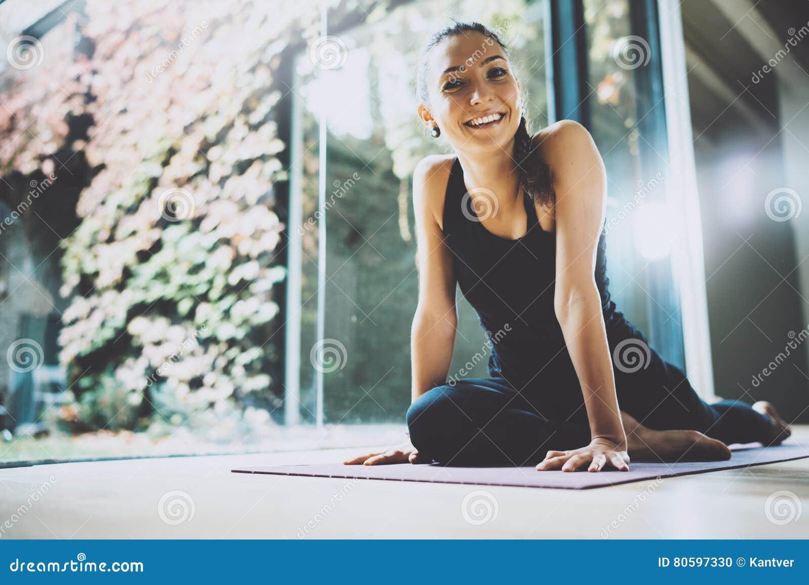 Portret wspaniałej młodej kobiety ćwiczy joga salowy Piękna dziewczyna ono uśmiecha się podczas praktyki klasy Calmness i relaksu