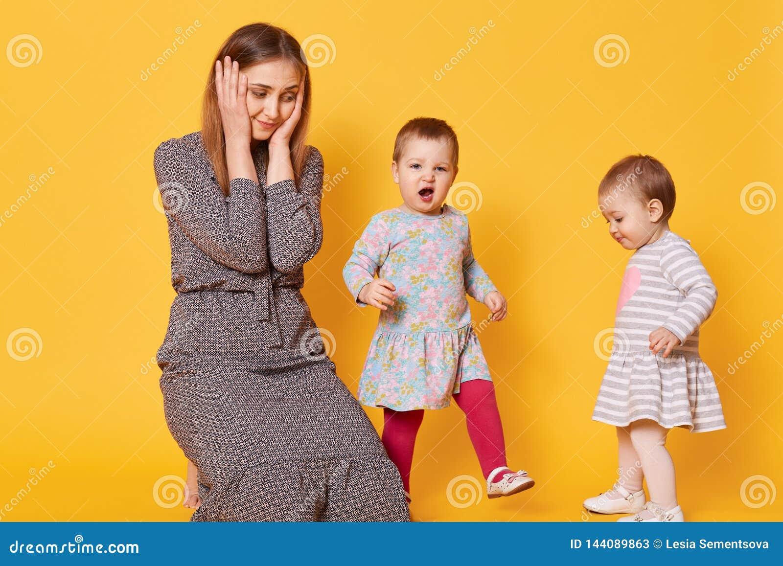 Portret zaakcentowana zmęczona matka która zakrywa jej ucho z dwa rękami od dzieciaka głośny krzyczeć, cierpi od okropnej migreny