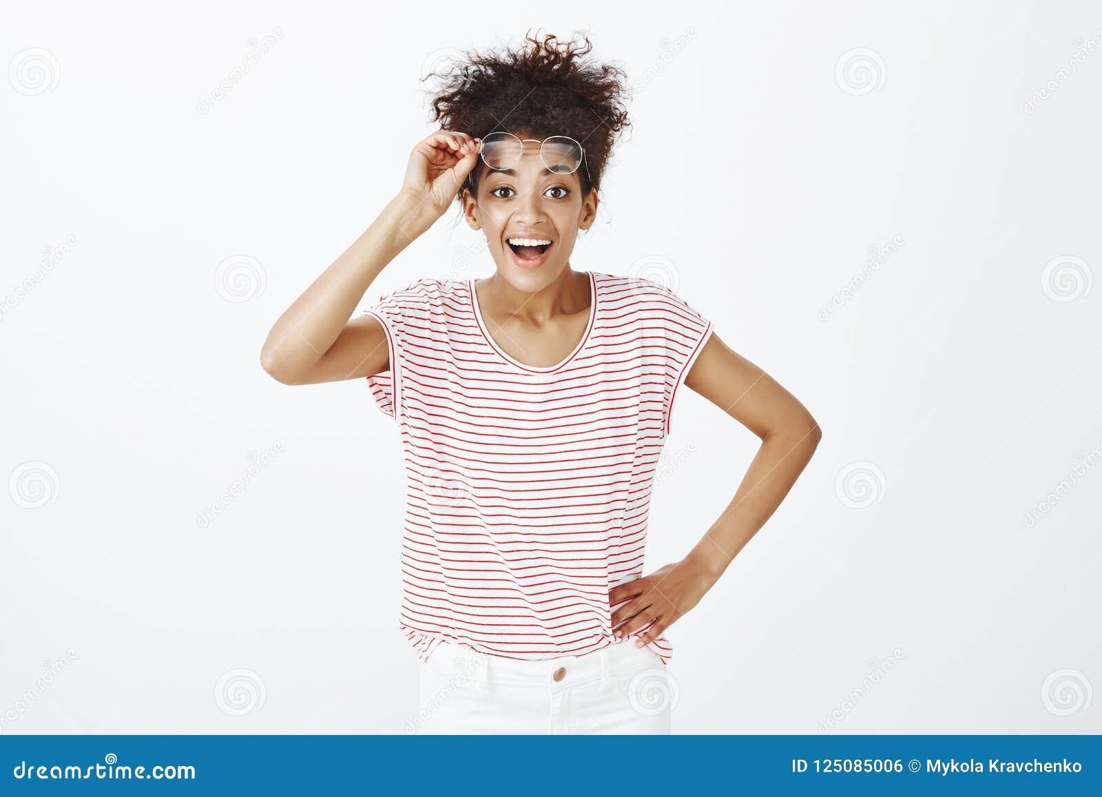 Portret zadowolona życzliwa kobieta z kędzierzawym rozczesanym włosy, trzymający rękę na biodrze, brać daleko szkło i ono uśmiech