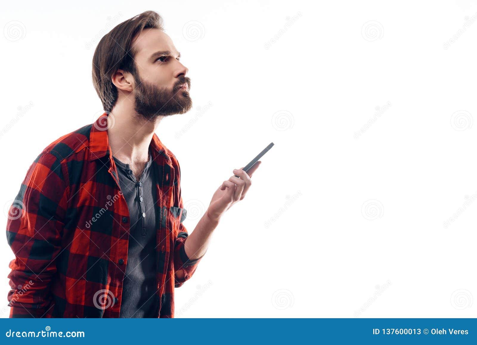 Portret Zadumany mężczyzny mienia telefon i Patrzeje W górę