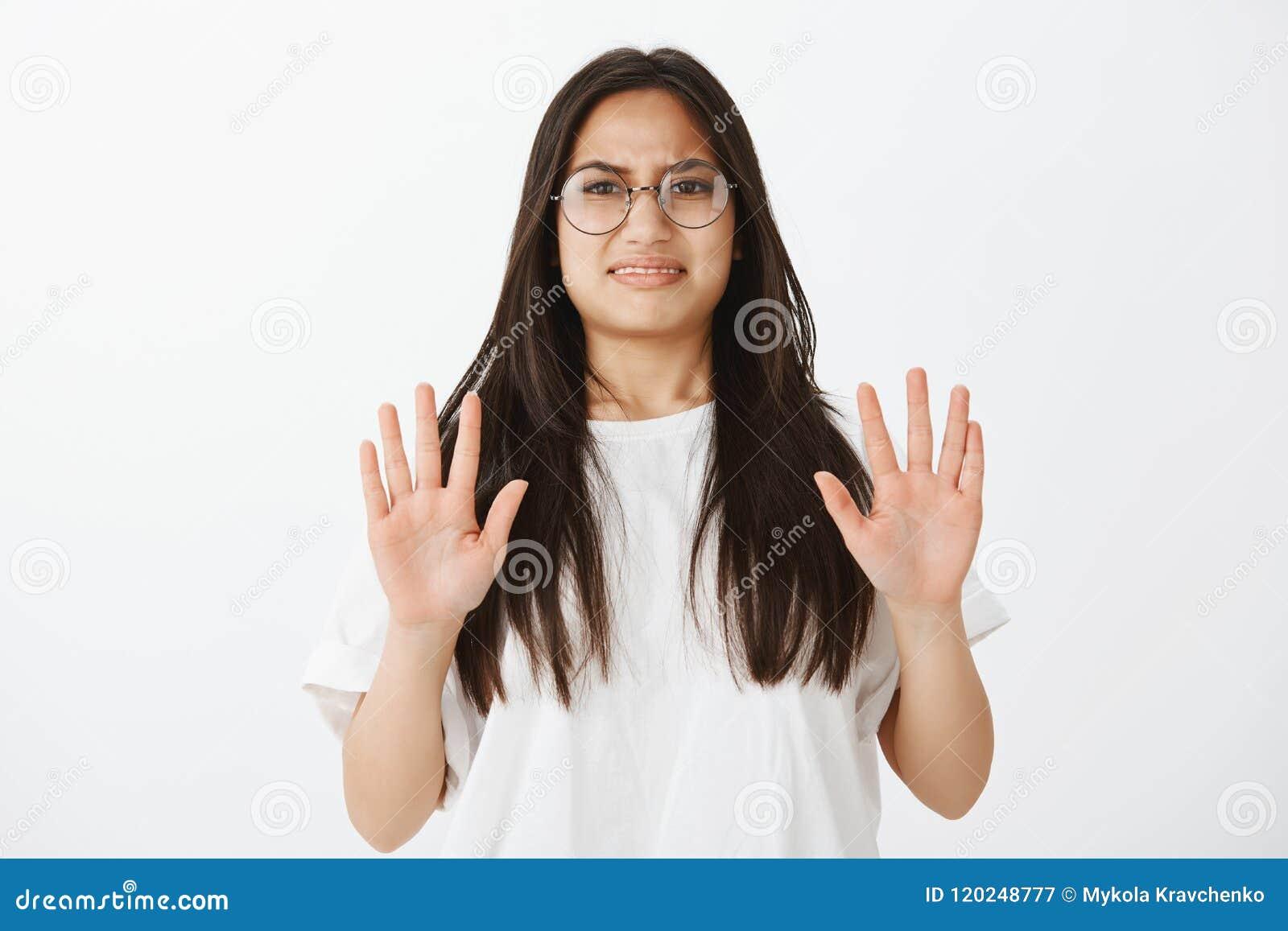 Portret zdegustowana nieporuszona śmieszna dziewczyna w szkłach, robić stawia czoło od antypatii i niechęci podnosi palmy w żadny