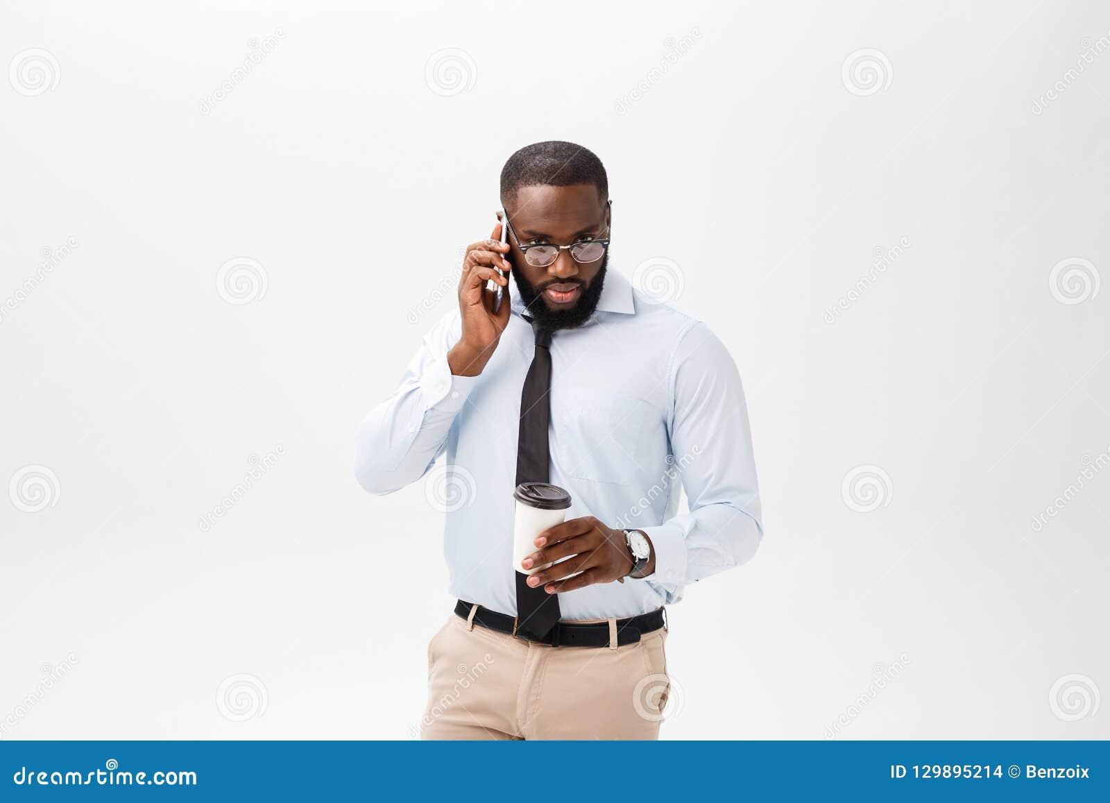 Portret zmieszany młody afrykański mężczyzna opowiada na telefonie komórkowym i gestykulować odizolowywających ubierał w białej k