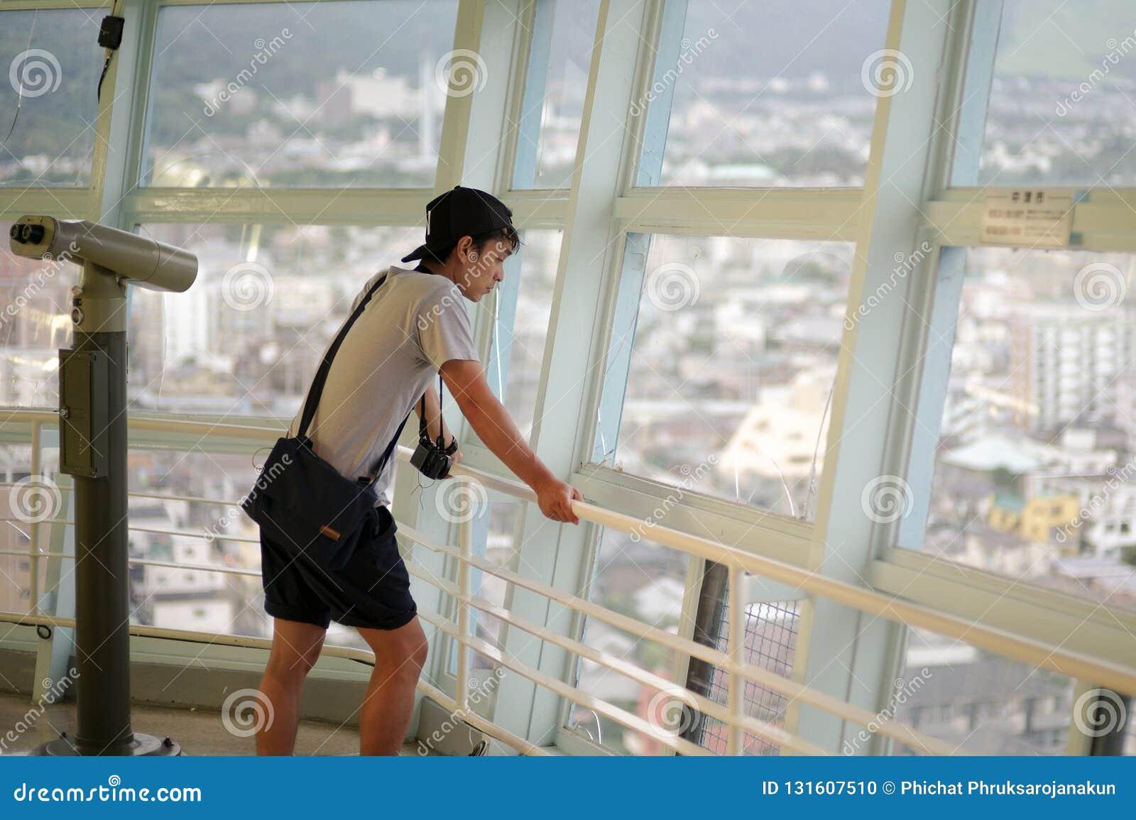 Portreta Azjatycki mężczyzna patrzeje miasto widok od wysoki wierza, Beppu wierza w Japonia,